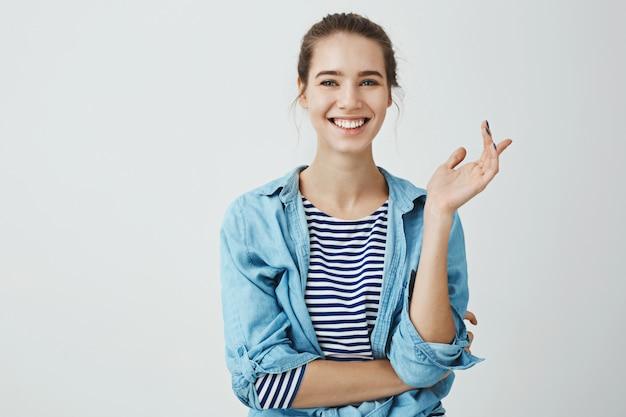 Lachen lindert alltägliche probleme. charmante frau im trendigen outfit mit brötchenfrisur, die gestikuliert, während sie mit freund spricht, mit gekreuzter hand über körper steht und breit lächelt