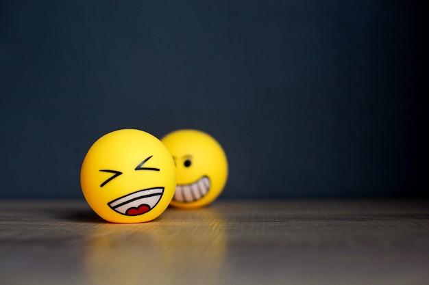 Lachen sie emoticon und verschwommenes smiley-emoticon auf schwarzem hintergrund