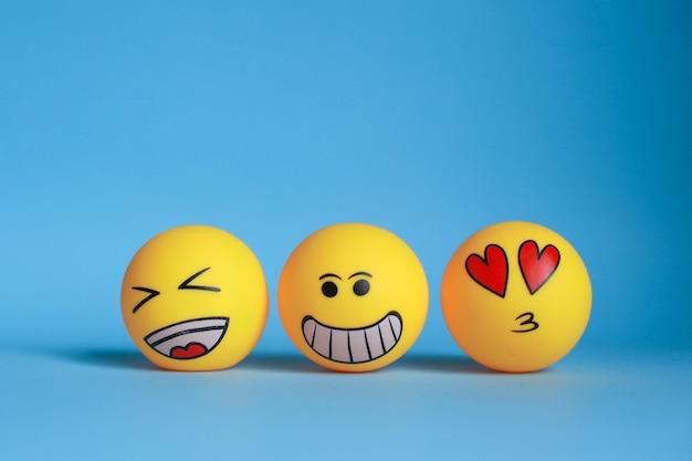 Lachen, smiley und liebesemoticon mit dem mund, der auf blauem hintergrund küsst