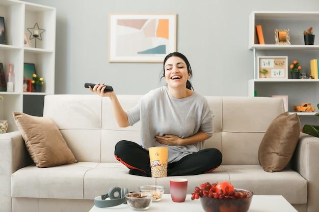 Lachend packte junges mädchen mit popcorn-eimer, das eine tv-fernbedienung hält, auf dem sofa hinter dem couchtisch im wohnzimmer