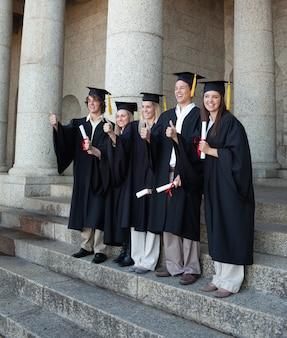 Lachende absolventen posieren den daumen nach oben