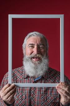 Lachende ältere frau, die weiße rahmengrenze vor seinem gesicht gegen roten hintergrund hält