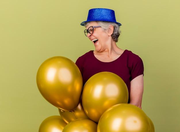 Lachende ältere frau in optischen gläsern steht mit heliumballons, die seite tragen partyhut lokalisiert auf olivgrüner wand mit kopienraum betrachten