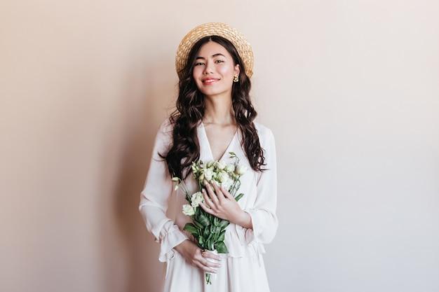 Lachende asiatische frau, die weiße blumen hält. vorderansicht der japanischen frau im strohhut, der mit blumenstrauß aufwirft.