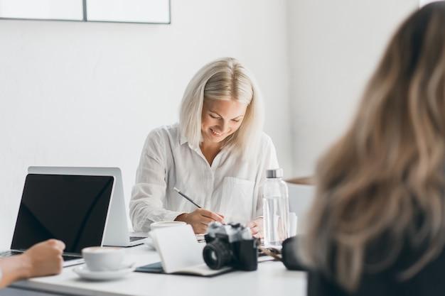 Lachende blonde frau im weißen hemd, das unten schaut, während sie etwas schreibt. innenporträt des beschäftigten freiberuflichen weiblichen spezialisten, der am arbeitsplatz mit laptop und kamera aufwirft.