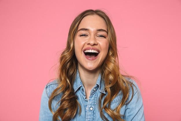 Lachende blonde frau in jeanshemd, die mit offenem mund über rosa wand nach vorne schaut