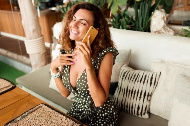 Lachende brünette frau im stilvollen kleid, das per handy im tropischen café nahe strand spricht.