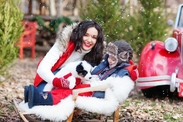 Lachende brünette mutter und ihr sohn sitzen im schlitten mit husky-welpen vor santas auto