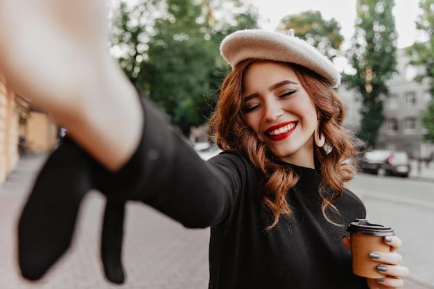 Lachende charmante frau mit hellem make-up, das im herbst selfie macht. frohes lockiges französisches mädchen, das kaffee auf der straße trinkt.