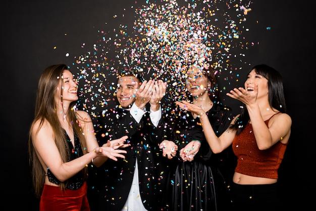Lachende damen und kerl in abendkleidern werfen konfetti