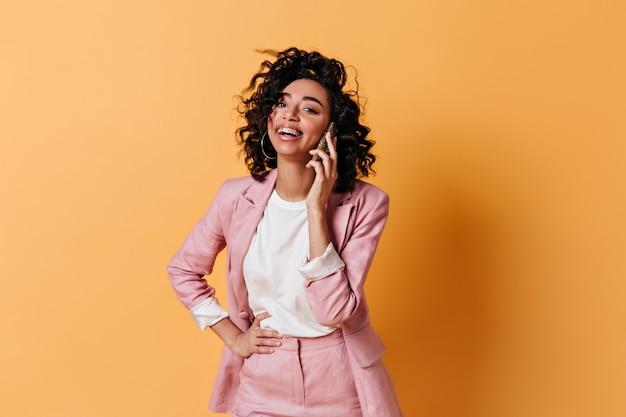 Lachende elegante frau im anzug, die auf smartphone spricht