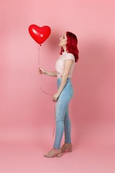 Lachende, entzückte frau mit roten haaren und jeans schaut auf einen fliegenden roten ballon in ihrer hand