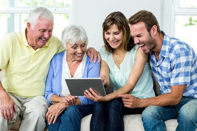 Lachende familie beim schauen in der digitalen tablette
