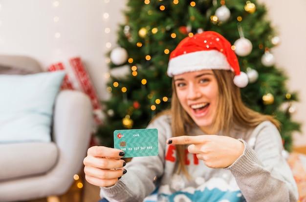 Lachende festliche frau, die auf kreditkarte zeigt
