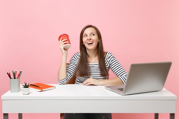 Lachende frau, die eine tasse kaffee oder tee hält und an einem projekt arbeitet, das im büro sitzt, mit pc-laptop einzeln auf pastellrosa hintergrund. erfolgsgeschäftskarrierekonzept. kopieren sie platz für werbung.