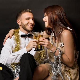 Lachende Frau, die Mann in der Abendkleidung mit Gläsern von Getränken umarmt