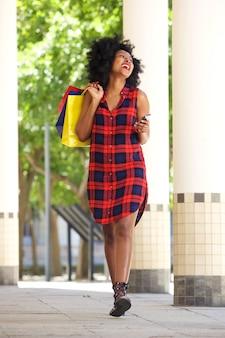 Lachende frau, die mit einkaufstaschen und handy geht