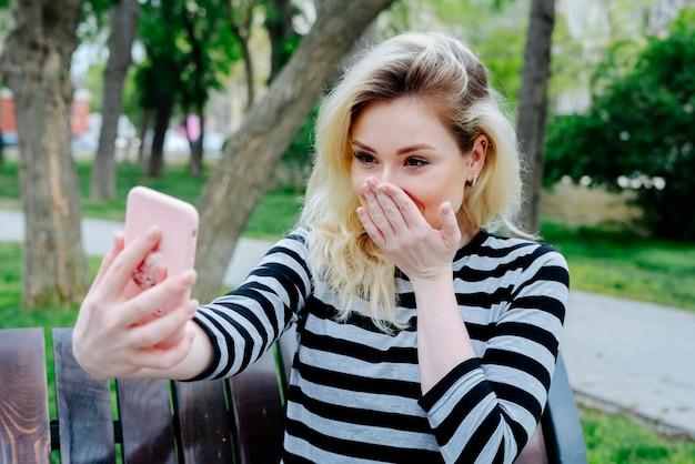 Lachende frau, die selfie mit smartphone nimmt, während draußen im freien auf einer bank im gestreiften oberteil sitzt
