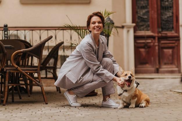 Lachende frau im grauen anzug lacht und spielt mit hund. charmante kurzhaarige dame in stilvoller jacke und hose, die mit corgi lächelt und posiert