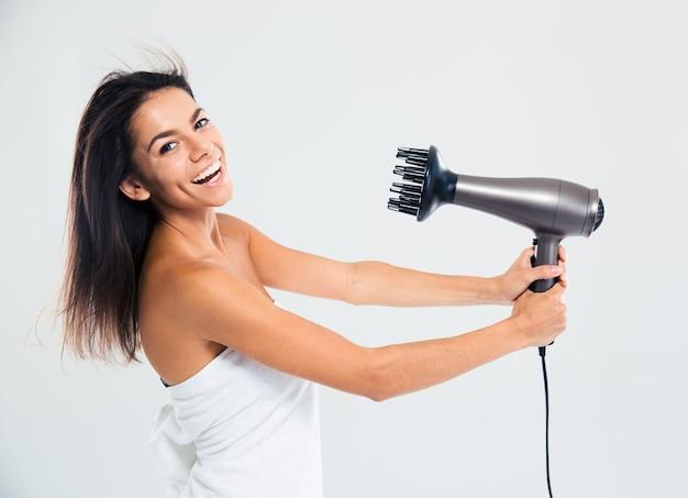 Lachende frau im handtuch, das ihre haare trocknet