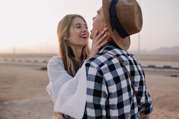 Lachende frau im weißen hemd streichelt ihrem freund ins gesicht und schaut mit liebe auf seine augen. junger mann, der kariertes hemd trägt, das zeit mit freundin am romantischen datum im freien am morgen verbringt