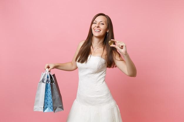 Lachende frau im weißen kleid hält bitcoin-metallmünze in goldener farbe, mehrfarbige pakettasche mit einkäufen nach dem einkaufen
