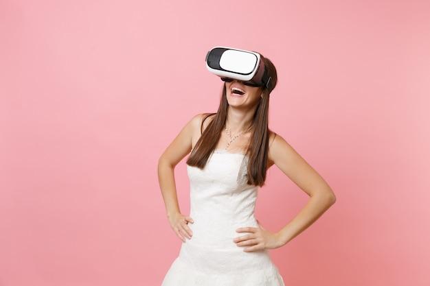 Lachende frau im weißen kleid und headset der virtuellen realität, die mit angewinkelten armen steht