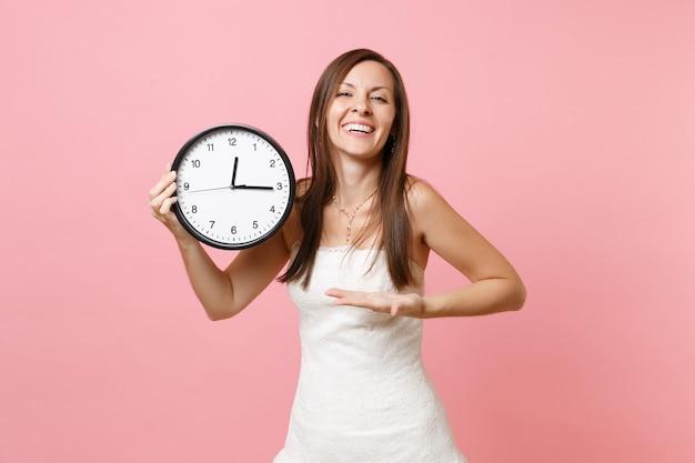 Lachende frau im weißen kleid zeigt hand auf runden wecker