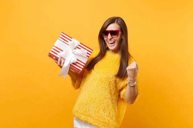 Lachende frau in roten brillen, die siegergeste macht und eine rote schachtel mit geschenkgeschenk hält, die den urlaub einzeln auf hellgelbem hintergrund genießt. menschen aufrichtige emotionen, lebensstil. werbefläche.