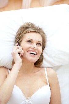Lachende frau in unterwäsche am telefon sprechen