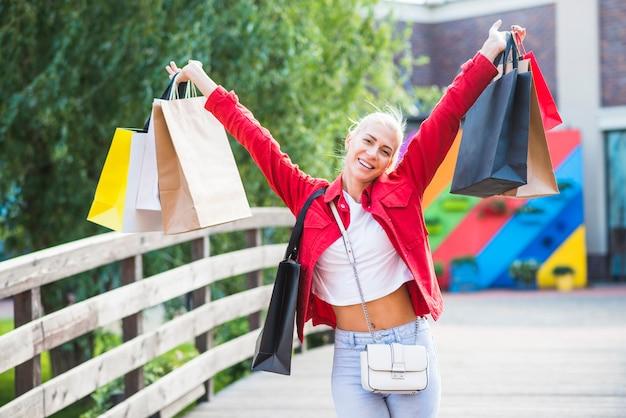 Lachende frau mit einkaufstüten