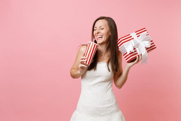 Lachende frau mit geschlossenen augen im weißen kleid hält eine rote schachtel mit geschenk, trinkt cola oder soda aus plastikbecher