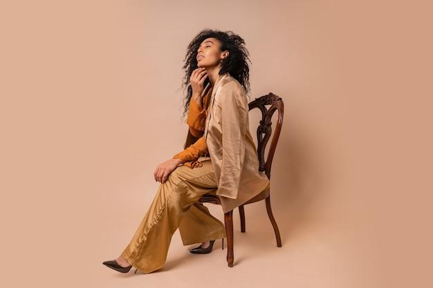 Lachende frau mit perfektem lockigem haar in eleganter orangefarbener bluse und seidenhose, die auf vintage-stuhl sitzt