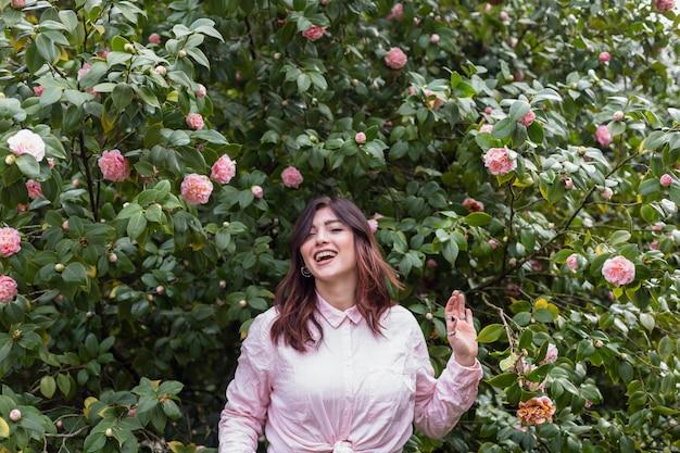 Lachende frau nahe vielen rosa blumen, die auf grünen zweigen wachsen