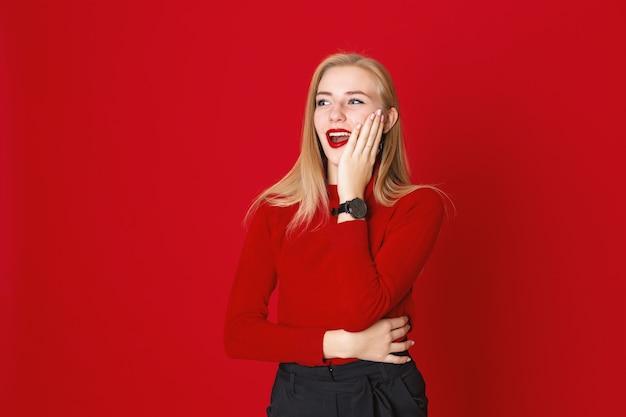 Lachende frau steht auf einem roten hintergrund in der zufälligen kleidung, die ihr gesicht berührt
