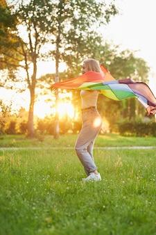 Lachende frau tanzt mit lgbt-flagge hinter dem rücken