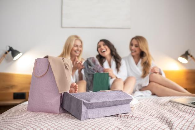 Lachende frauen auf dem bett umgeben von einkaufstüten