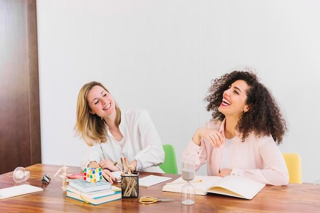Lachende frauen, die bei tisch studieren