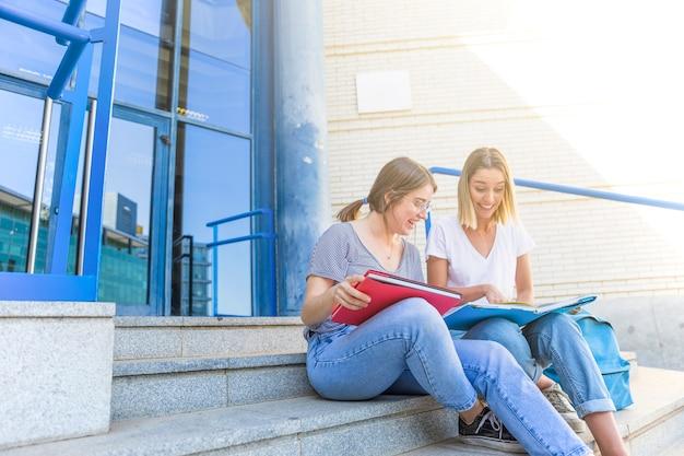 Lachende frauen, die nahe hochschulgebäude studieren
