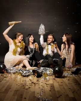 Lachende Frauen und Mann am Abend tragen mit Gläsern von Getränken auf dem Boden