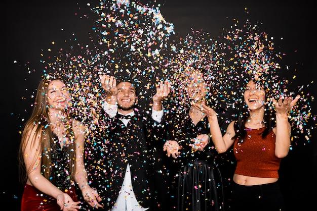 Lachende frauen und mann in abendkleidern werfen konfetti