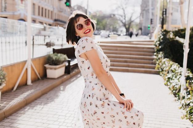 Lachende freudige frau in der trendigen sonnenbrille, die spaß im sonnigen sommertag hat. außenporträt des angenehmen mädchens mit kurzem haarschnitt trägt weißes kleid im warmen frühlingsmorgen.