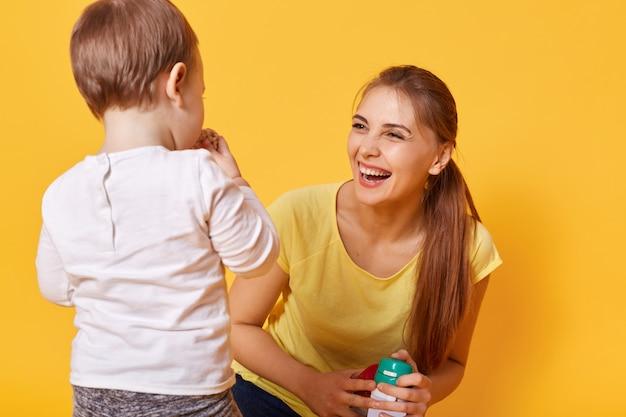 Lachende freudige frau spielt mit ihrer kleinen süßen tochter