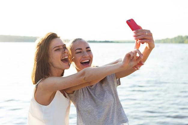 Lachende freunde beim aufnehmen eines selfies