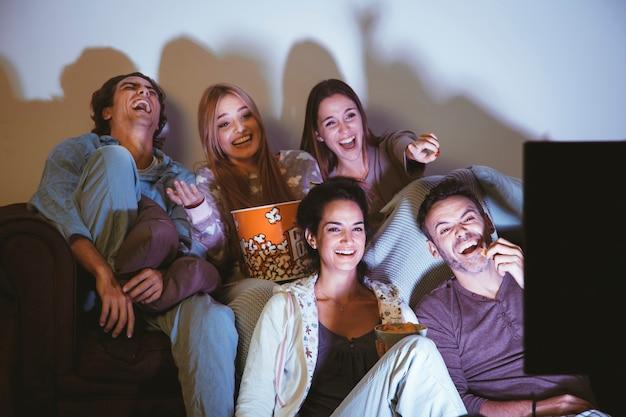 Lachende freunde, die einen film ansehen