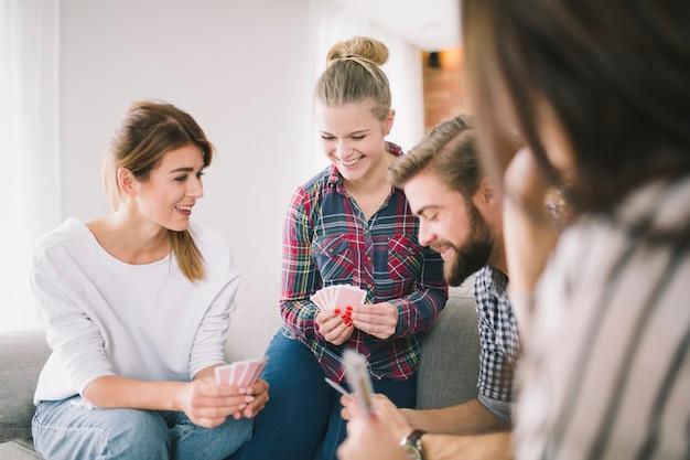 Lachende freunde, die kartenspiel genießen