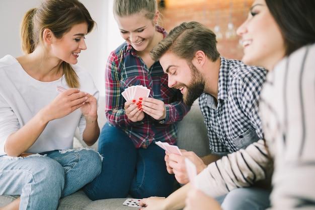 Lachende freunde, die zu hause spielkarten spielen