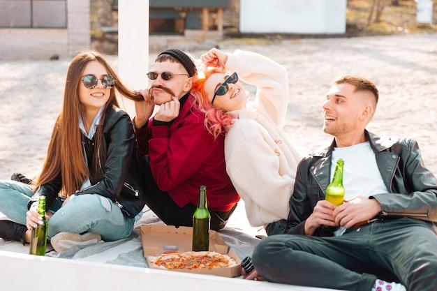 Lachende freunde, die zusammen spaß auf einem picknick haben