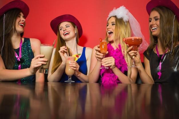 Lachende freunde in einer henne nacht trinken cocktails