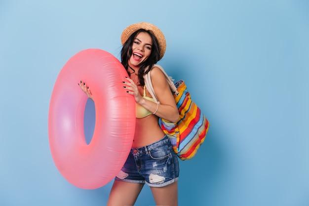 Lachende gebräunte frau, die tasche und schwimmkreis hält